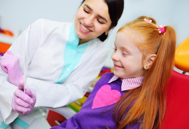 Der zahnarzt der kinder untersucht die zähne und den mund des kindes - ein nettes rothaariges mädchen, das in einem zahnmedizinischen stuhl sitzt