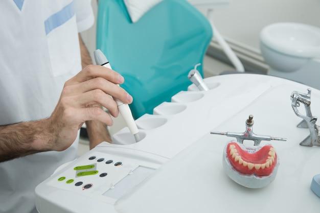 Der zahnarzt hält das instrument in der hand