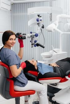 Der zahnarzt schaut durch ein mikroskop und operiert den patienten.