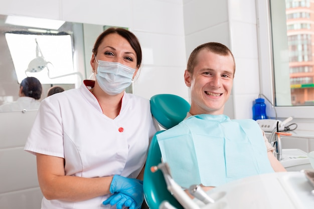 Der zahnarzt und ihre glückliche patientin schauen in die kamera und lächeln. empfang beim zahnarzt, gesunde zähne, glücklicher patient, schöne zähne.
