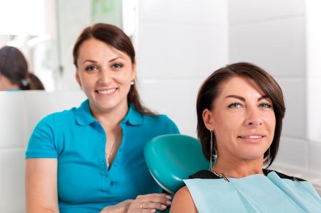 Der zahnarzt und ihre glückliche patientin schauen in die kamera und lächeln
