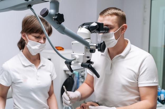 Der zahnarzt untersucht die zähne des patienten mit einem zahnmikroskop. moderne medizinische geräte. konzept der oralen behandlung. nahaufnahme. selektiver fokus.