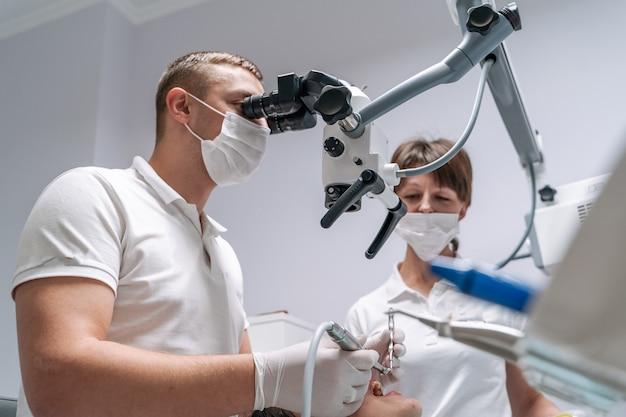 Der zahnarzt untersucht die zähne des patienten mit einem zahnmikroskop.