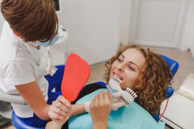 Der zahnarzt vergleicht die zahnfarbe des patienten mit proben für die bleaching-behandlung