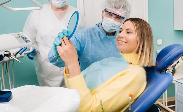 Der zahnarzt zeigt dem kunden die ergebnisse seiner arbeit im spiegel.