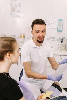 Der zahnarzt zeigt einer süßen frau eine röntgenaufnahme der zähne des patienten. empfang beim zahnarzt.