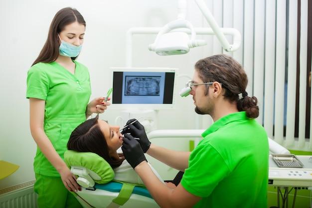 Der zahnarztmann behandeln zähne zum kunden im zahnmedizinischen büro