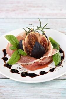 Der zarte geschmack von prosciutto wird ideal mit der süße von feigen kombiniert.