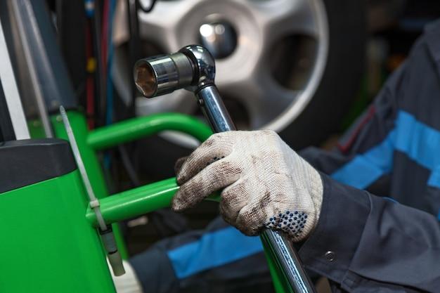 Der zauberer hält den verstellbaren schraubenschlüssel der mann repariert die scheibenbremsmaschine nahaufnahme