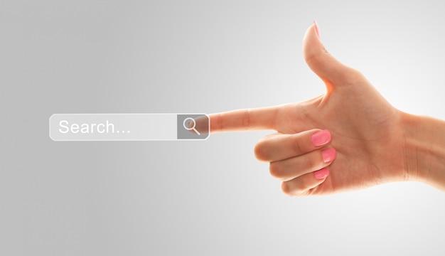 Der zeigefinger einer weiblichen hand zeigt auf das suchfeld
