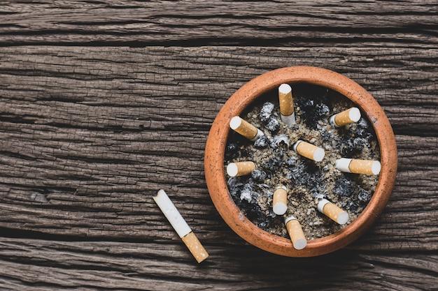 Der zigarettenstummel im topf steht auf einem alten holzfußboden.