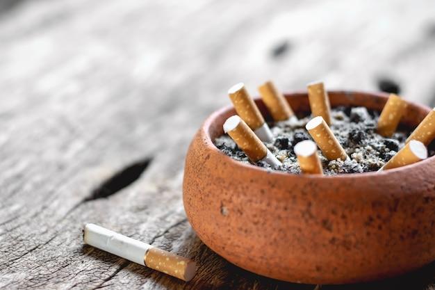 Der zigarettenstummel im topf wird auf einen alten holzboden gestellt.