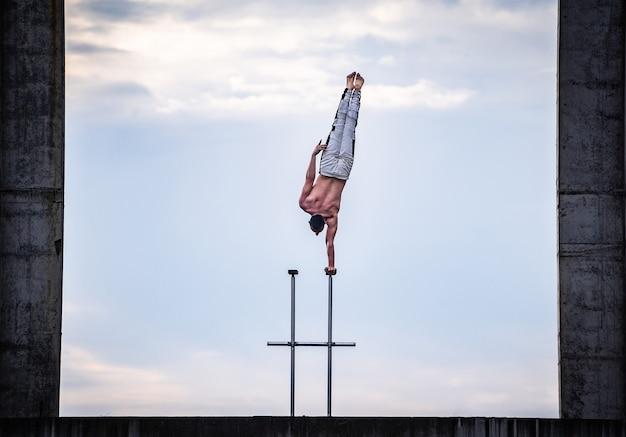 Der zirkuskünstler hält einerseits das gleichgewicht auf dem himmel und dem hintergrund des industriebaus. konzept von handstand, performance und kunst.