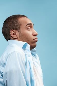 Der zweifelhafte afroamerikanische mann schaut erschrocken gegen den blauen raum