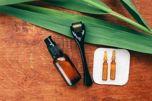 Dermaroller und serum neben einer anti-aging-gesichtscreme beauty-industrie close-up dermaroller für die medizinische mikronadeltherapie