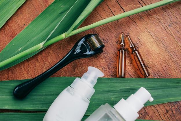 Dermaroller und serum neben einer anti-aging-gesichtscreme beauty industry close-up