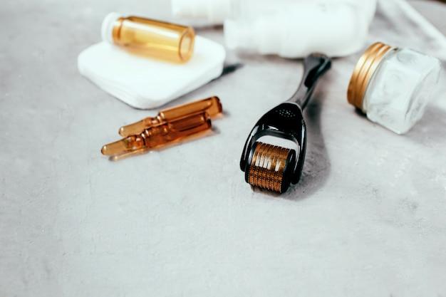 Dermaroller und serum neben einer anti-aging-gesichtscreme