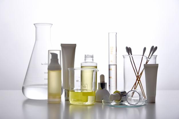 Dermatologe formuliert und mischt pharmazeutische hautpflege, kosmetische flaschenbehälter und wissenschaftliche glaswaren. erforscht und entwickelt das konzept für schönheitsprodukte.