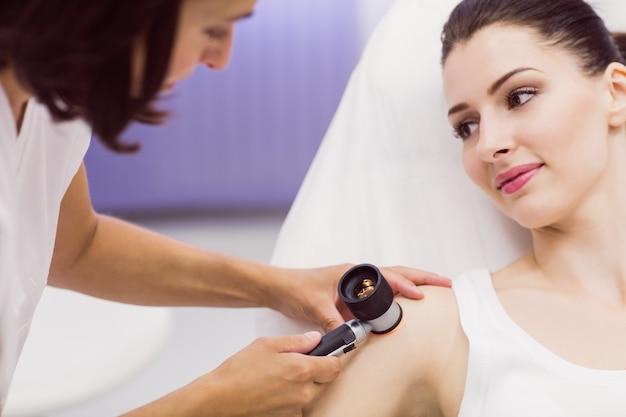 Dermatologe untersucht die haut des patienten mit dem dermatoskop