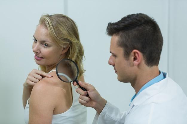 Dermatologe untersucht maulwurf mit lupe