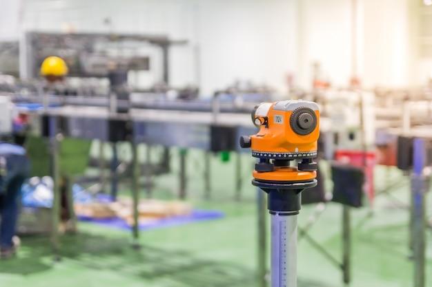 Des theodolitniveaus werkzeug des baulandmessers ausrüstungsausrüstungs während der arbeitskräfte, die maschine installieren