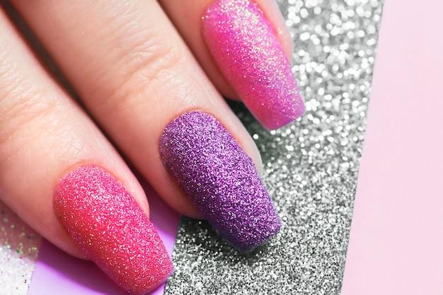Design auf langen nägeln aus mehrfarbigen pailletten