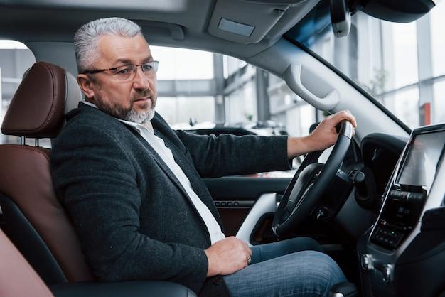 Design betrachten. älterer geschäftsmann in der offiziellen kleidung, die neues luxusauto im autosalon versucht