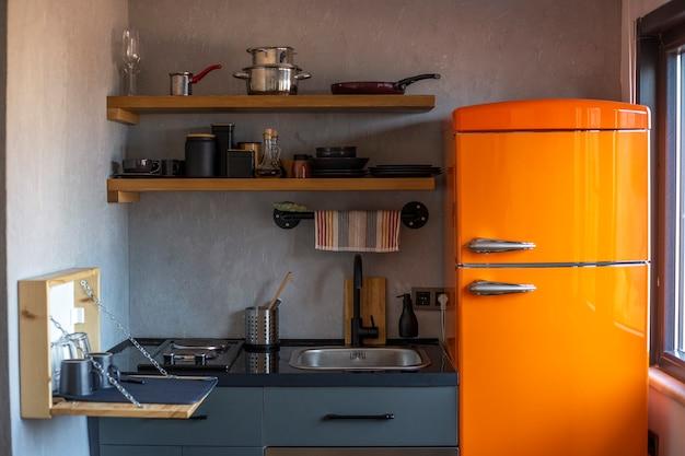 Design einer kleinen loftstyle-küche mit einem orangefarbenen kühlschrank