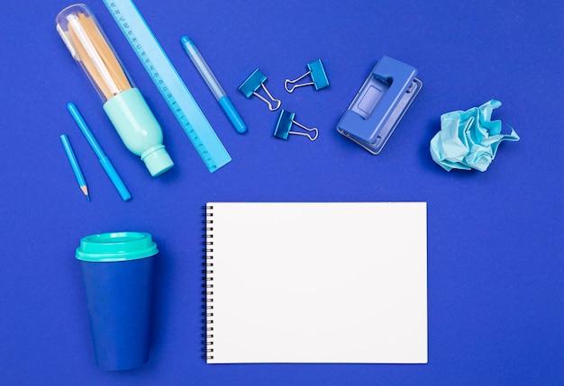 Design konzept. leeres skizzenbuch mit zubehör auf blauem hintergrund mit layout