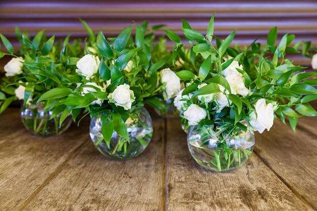 Design und dekoration der hochzeitsfeier mit weißen rosen, grünen blättern, kerzen