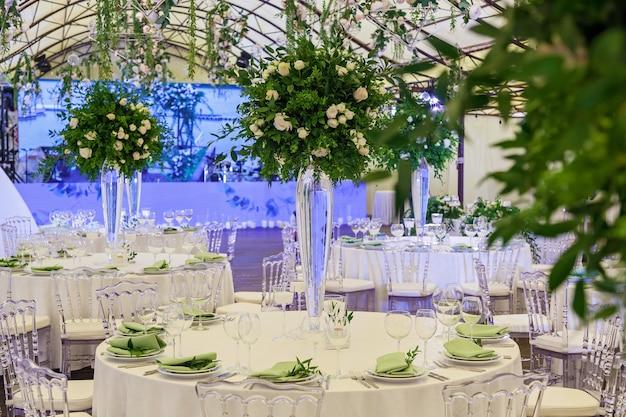 Design und dekoration von hochzeitsfeiern mit weißen rosen und grünen blättern