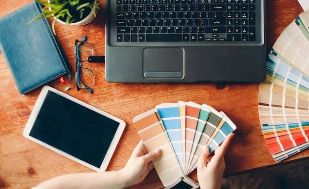 Designer arbeitet von zu hause aus auf dem tisch. der desktop des innenarchitekten. farbpalette.