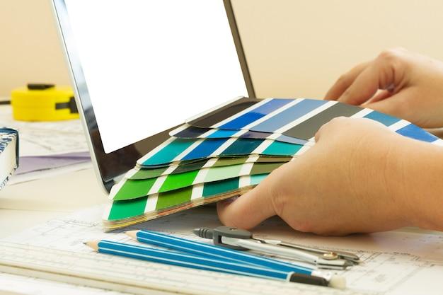 Designer-arbeitstisch - nahaufnahme von designer-händen, die farbkarten halten, kopienraum auf leerem bildschirm
