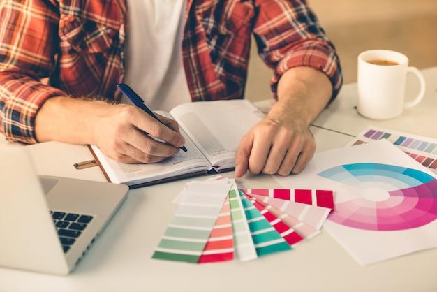 Designer benutzt laptop und schreibt in sein notizbuch
