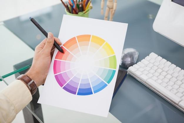 Designer, der am schreibtisch unter verwendung eines farbrads arbeitet