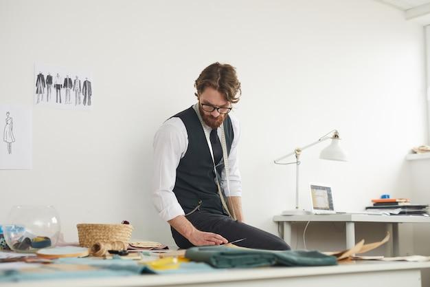 Designer, der am tisch sitzt und mit skizzen arbeitet, macht die kleidung