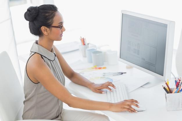 Designer, der an ihrem schreibtisch unter verwendung des computers arbeitet