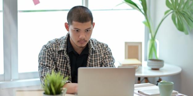 Designer, der an seinem projekt bei der anwendung des laptops arbeitet