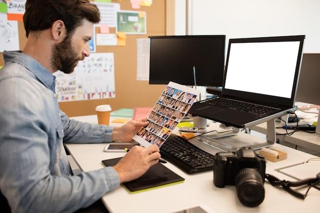 Designer, der fotos mit digitalisierer und laptop zeichnet