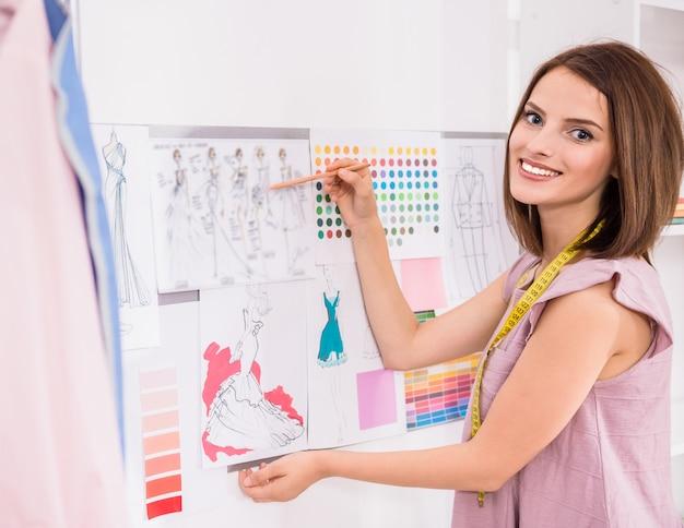 Designer, der in ihrem büro und in lächeln steht