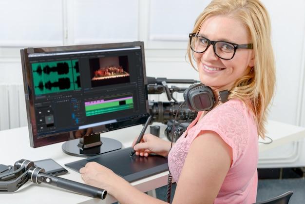 Designer der jungen frau, der computer für das videobearbeiten verwendet