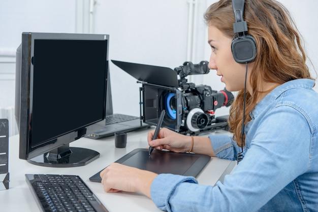 Designer der jungen frau, der grafiktablett für die videobearbeitung verwendet