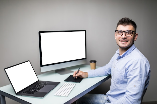 Designer des jungen mannes, der foto auf computer im büro bearbeitet