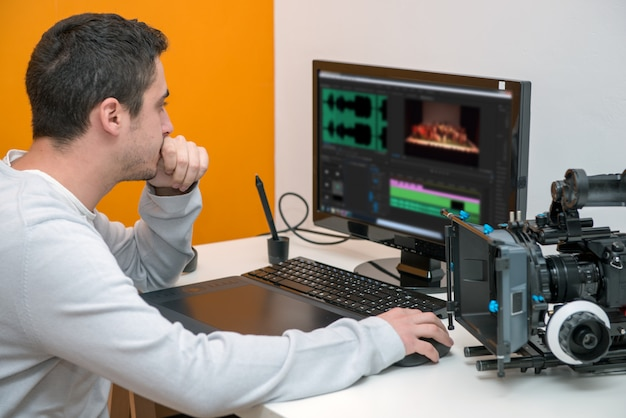 Designer des jungen mannes, der grafiktablett für die videobearbeitung verwendet