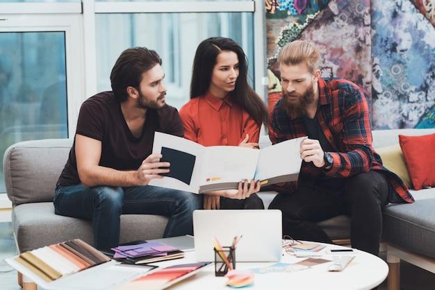 Designer hilft einem mann und einer frau bei der auswahl von farbmustern.