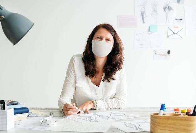 Designer in einer maske am neuen normalen büroarbeitsplatz