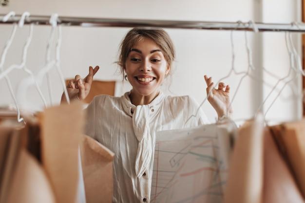 Designer in weißer bluse drückt die daumen