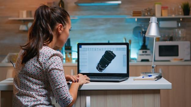 Designer-ingenieur analysiert neuen prototyp des 3d-modells der anlage, die von zu hause aus arbeitet. industrielle arbeiterin, die die turbinenidee auf dem pc studiert, die cad-software auf dem gerätedisplay zeigt