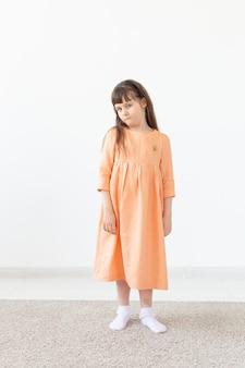 Designer-konzept für kindheit, kinder und kleidung - kleines mädchen, das in modekleidung im studio aufwirft