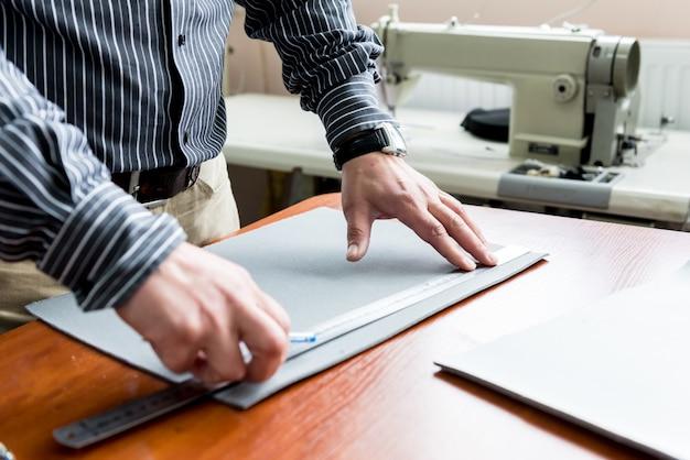 Designer schneider nähen sitzbezüge. mann benutzen nähmaschine für seine arbeit.
